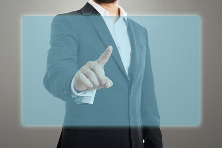 businessman touching at empty virtual screen over dark background photo