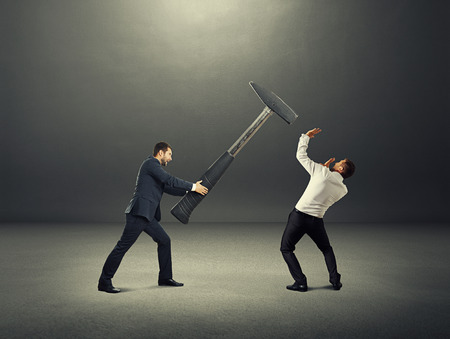 angry businessman: angry screaming businessman holding big hammer and hitting scared man. photo over dark background