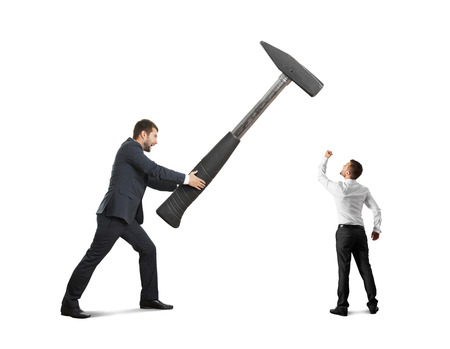 concept photo of conflict between businessmen. small businessman showing fist and looking at big hammer. isolated on white background photo