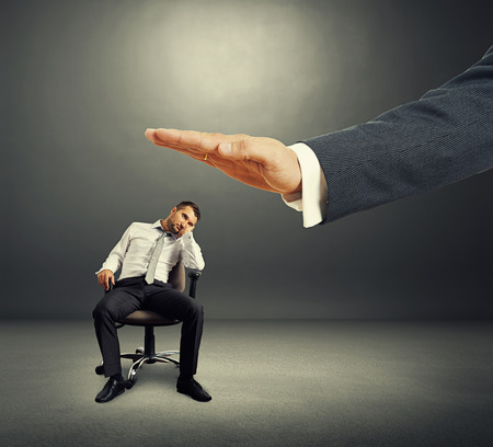 lazybones: big hand ready to hit lazy businessman on the office chair. photo over dark background