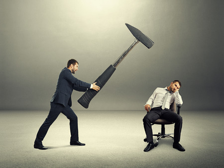 lazybones: displeased boss holding big hammer and screaming at lazy worker. photo in the dark room Stock Photo