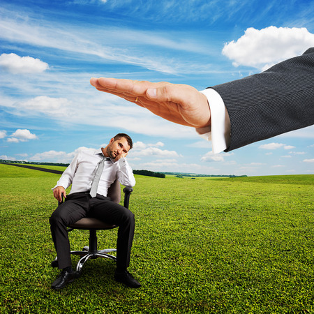 lazybones: big hand ready to hit lazy businessman on the chair. photo at outdoor Stock Photo