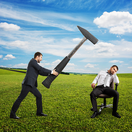 tedious: angry boss in the suit holding big hammer and screaming at lazy worker. photo at outdoor Stock Photo