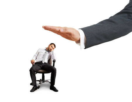 lazybones: big hand ready to slap lazy businessman on the chair. photo over white background