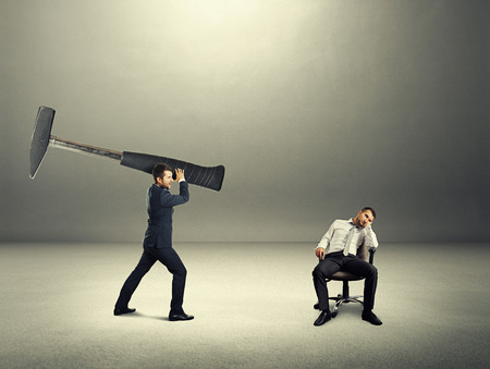 lazybones: dissatisfied boss holding big hammer and screaming at lazy worker. photo in the dark room