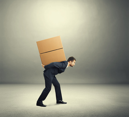 tired young businessman carrying on the back two heavy boxes. photo in the grey room photo
