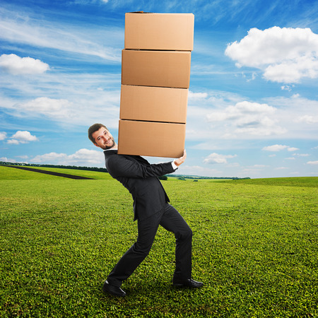 smiley young businessman looking at camera and carrying four heavy boxes on the hands. photo at outdoor photo