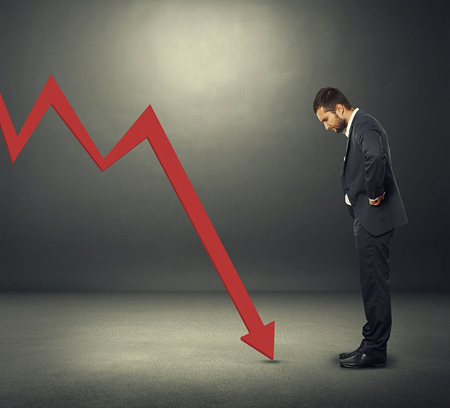 displeased businessman: displeased businessman looking at red downturn graph. photo over dark background Stock Photo