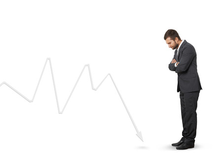 downturn: displeased man looking at downturn graph. isolated on white background