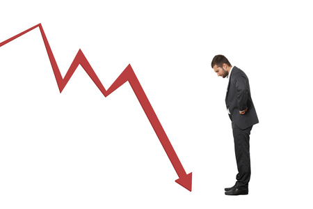 displeased businessman: displeased businessman looking at red downturn graph. isolated on white background
