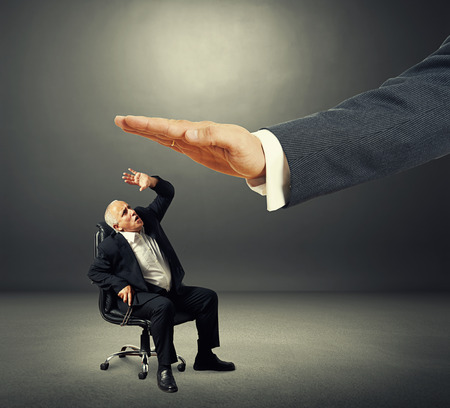 dominating: scared senior businessman looking up at big palm of his boss. photo over dark background Stock Photo