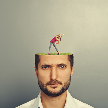 open minded: portrait of displeased man with cut head. small pretty woman doing fitness exercises on the green meadow in mans head. photo over grey background Stock Photo