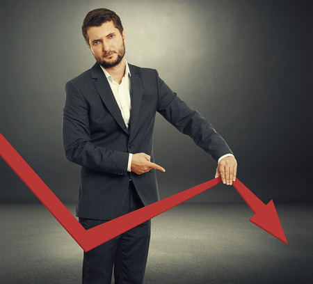 sad broker holding and pointing at falling down graph. photo over dark background photo