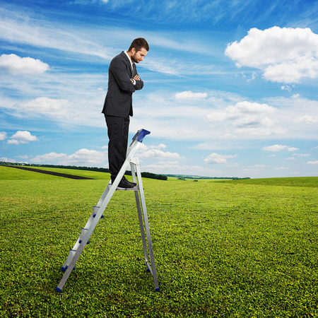 displeased businessman: displeased businessman standing on the pair of steps and looking down. photo over green field and blue sky