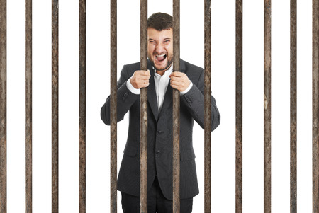 culpable: angry screaming businessman behind the prison cell over white background