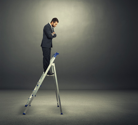 displeased businessman: displeased businessman standing on the stepladder and looking down in the dark room Stock Photo