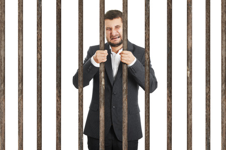 culpable: crying businessman behind the prison cell over white background