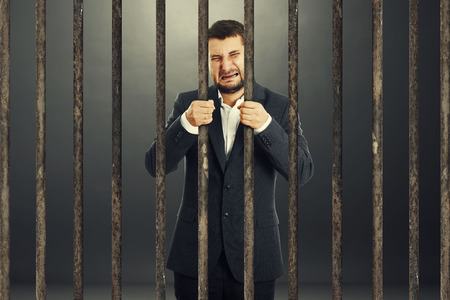 sentenced: crying businessman behind the prison cell over dark background Stock Photo