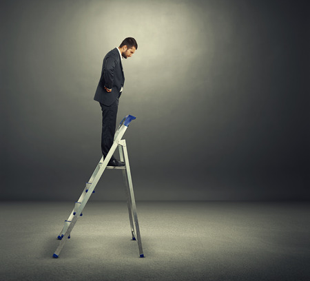 displeased businessman: displeased businessman in black suit standing on the stepladder and looking down in the dark room