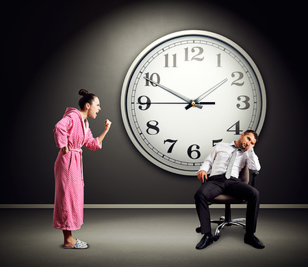 lazybones: angry wife screaming at lazy husband. photo in dark room with big clock on the wall Stock Photo