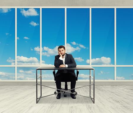wearied: sad man sitting in the empty office