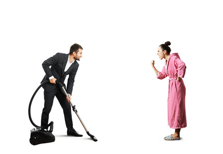 henpecked: smiley man in suit holding vacuum cleaner and looking at screaming angry wife in pink dressing gown. isolated on white