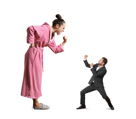 mujer enojada: luchar entre gritos de la mujer enojada y pequeño hombre loco. aislado en fondo blanco Foto de archivo