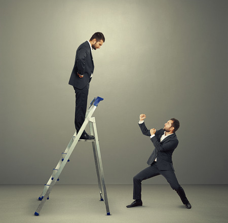 displeased businessman: displeased businessman on the stepladder looking down at man in fighting stance. photo in the grey studio Stock Photo