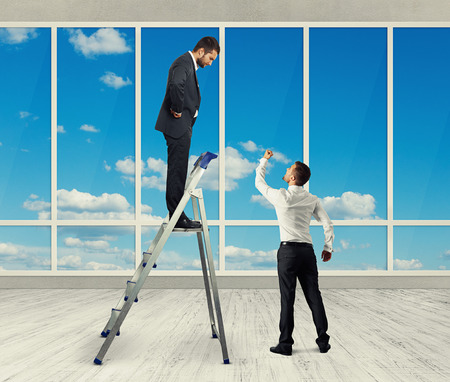 discontented: discontented businessman standing on stepladder and looking at angry screaming man. photo in the room with big windows Stock Photo