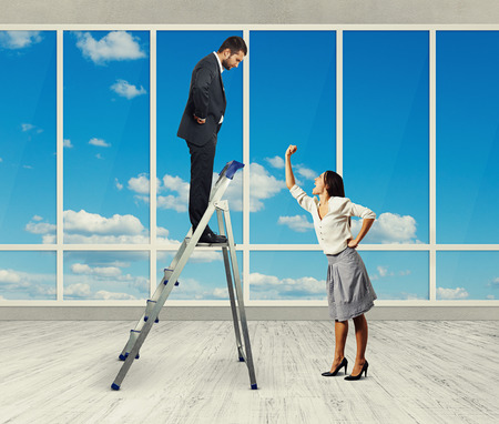 irritate: screaming woman and businessman on stepladder in the office with big windows