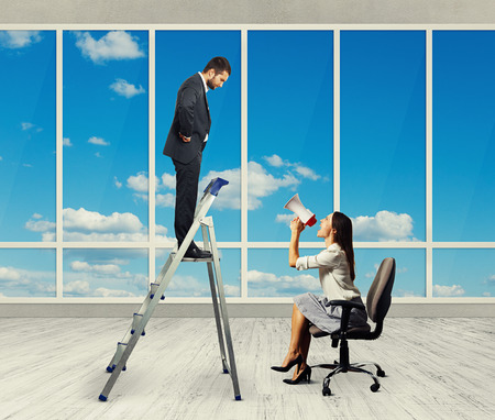 displeased businessman: emotional businesswoman with megaphone sitting on chair and screaming at displeased businessman on stepladder. photo in empty room with big windows
