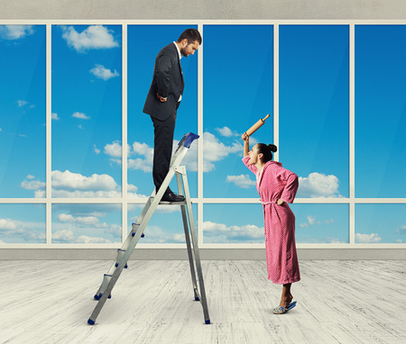 displeased businessman: dissatisfied man standing on stepladder and looking down at screaming woman with rolling pin. photo in room with big windows