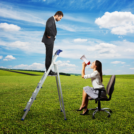 discontented: emotional woman with megaphone sitting on chair and screaming at discontented businessman on stepladder. photo at outdoor