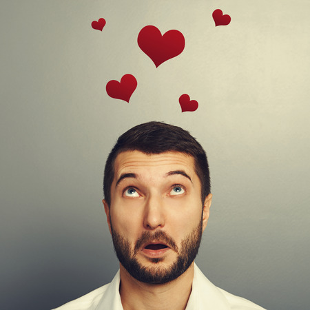 discredit: concept photo of man in love. amazed young man looking up at red hearts over grey background
