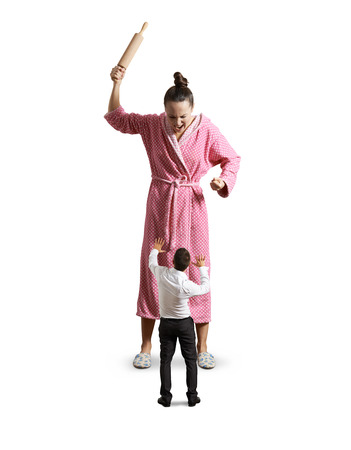angry housewife with rolling pin screaming at small startled husband. isolated on white background photo