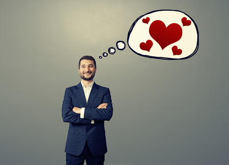 formal wear: portrait of handsome smiley businessman in formal wear with drawing speech bubble red hearts. concept photo of man in love. in over grey background Stock Photo
