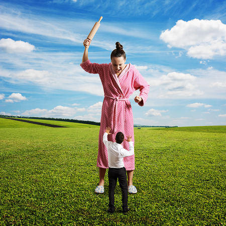 displeased housewife with rolling pin yelling at small startled husband. photo at outdoor photo