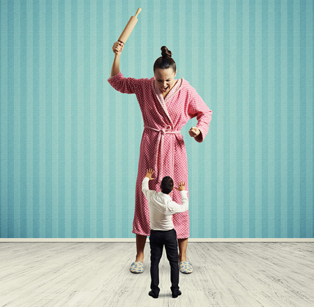 dissatisfied: dissatisfied housewife with rolling pin screaming at small startled husband Stock Photo