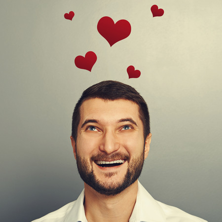 happy laughing man looking up at red hearts above his head over grey background photo