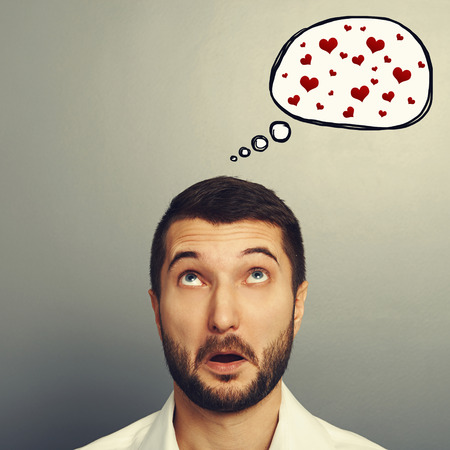discredit: amazed young man looking up at speech bubble with red hearts. portrait over grey background