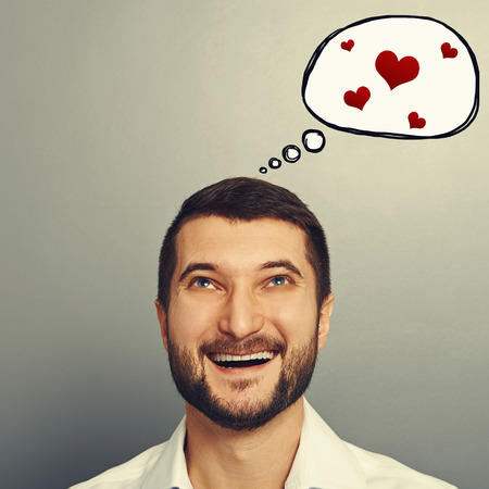 merriment: portrait of happy laughing man with speech bubble and red hearts over grey background