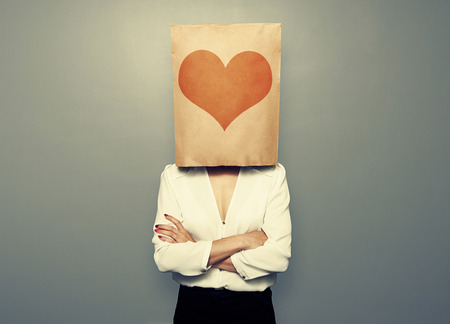 woman s bag: businesswoman hiding under paper bag with heart over dark background