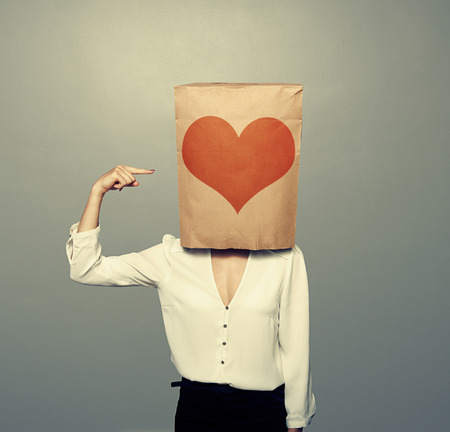 woman s bag: woman pointing at heart on paper bag over dark background Stock Photo