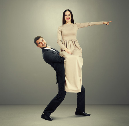 smiley happy man holding beautiful woman in long dress. woman smiling and pointing at something. photo in grey room photo