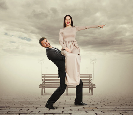 happy man holding his woman. smiley young woman in long dress pointing finger at something and looking at camera. photo at outdoor photo