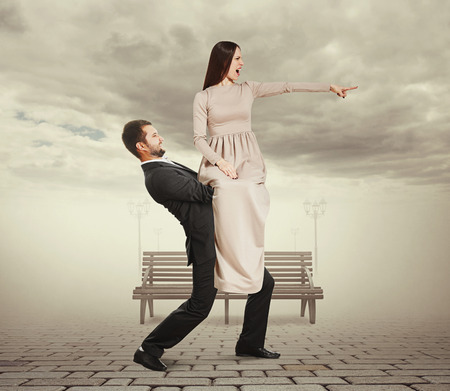 discontented: angry screaming woman sitting on tired man and pointing at something. photo at outdoor Stock Photo
