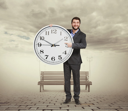 dial plate: smiley businessman holding big clock, pointing at dial plate and looking at camera. photo at outdoor Stock Photo