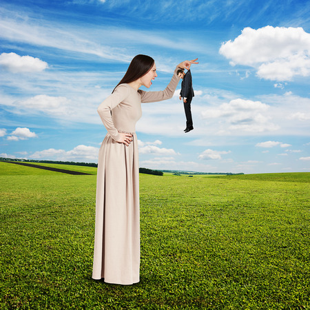 henpecked: yelling young woman with small man over green field and blue sky Stock Photo