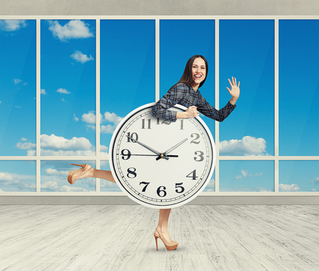 happy woman holding big clock, waving palm and laughing. photo in room with big windows photo