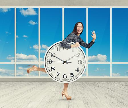 punctual: mujer feliz sostiene el reloj grande, agitando palmas y riendo. foto en la habitación con grandes ventanas
